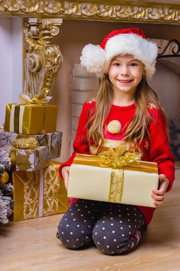 Fille heureuse mignonne dans le chapeau rouge tenant le présent photos stock