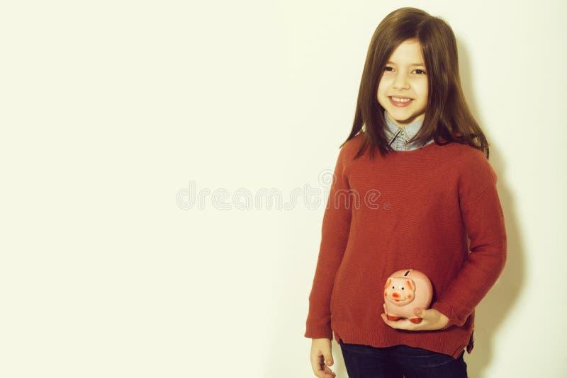 Fille heureuse, mignonne, petite, petite souriant avec la tirelire photographie stock libre de droits