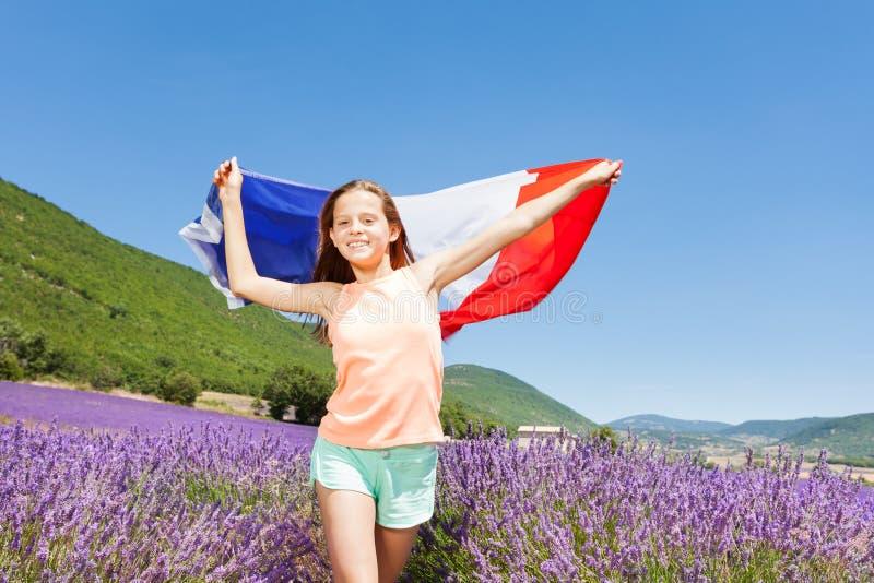 Fille heureuse ondulant le drapeau français dans le domaine de lavande images libres de droits