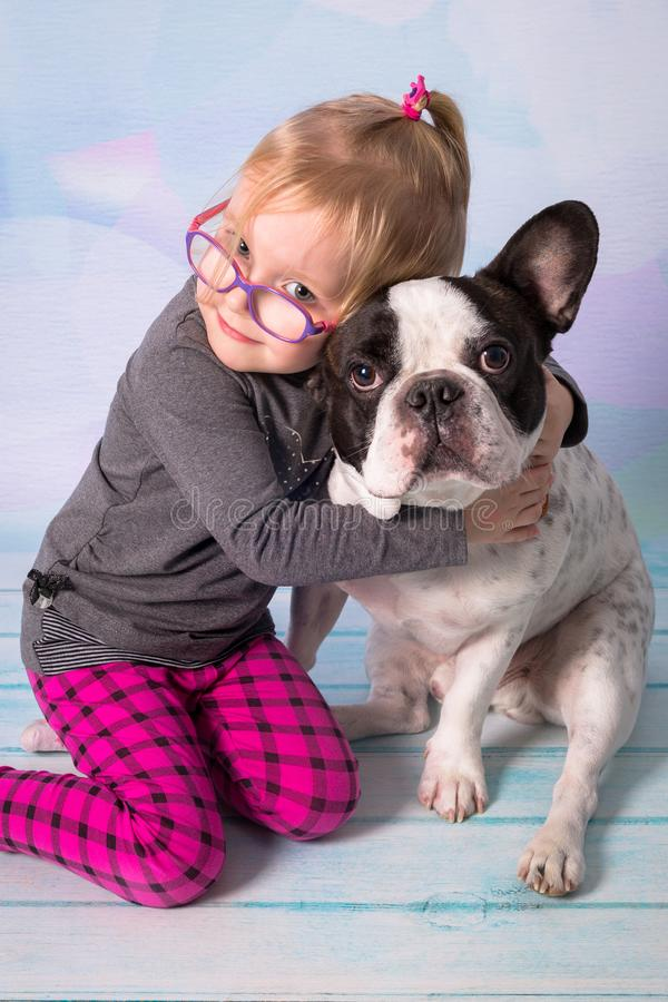 Fille heureuse posant avec le beau bouledogue français photographie stock