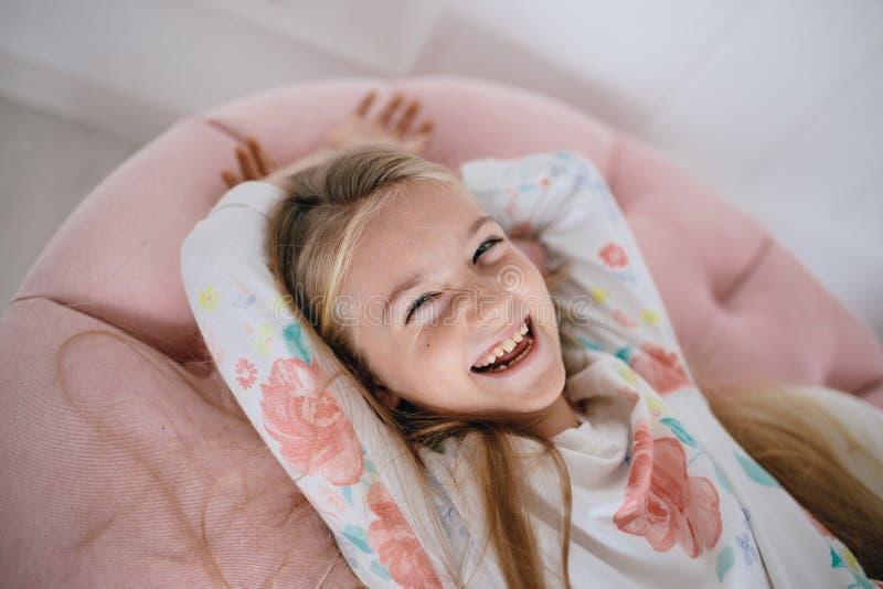 Fille heureuse riante se trouvant sur un oreiller rose images libres de droits