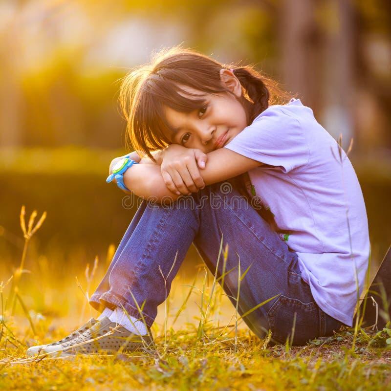 Fille heureuse s'asseyant sur l'herbe dans le jardin photos stock