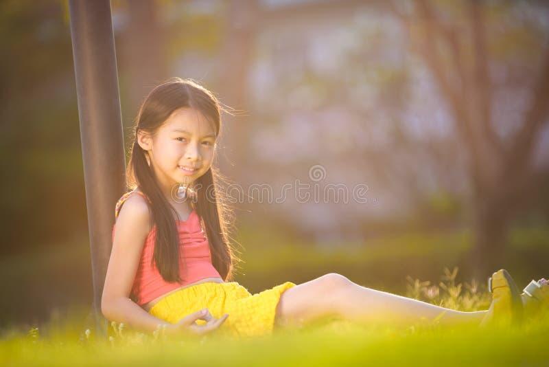 Fille heureuse s'asseyant sur l'herbe dans le jardin image libre de droits