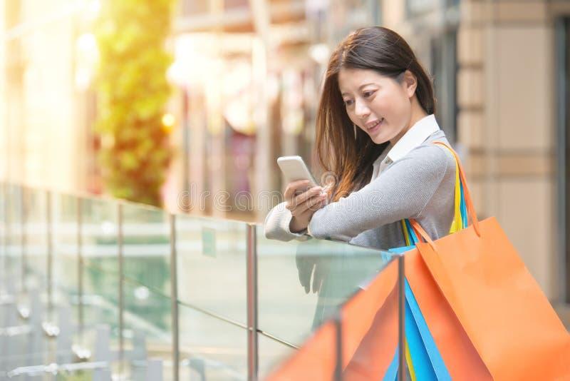 Fille heureuse se tenant avec des achats regardant le téléphone photographie stock