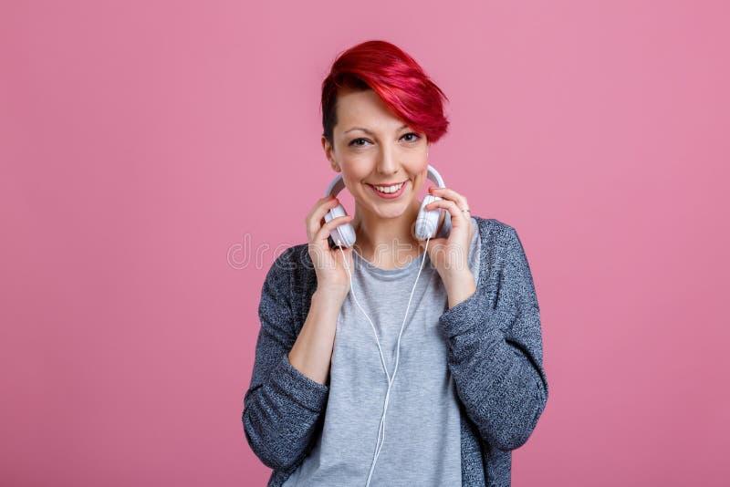 Fille heureuse, se tenant dessus sur les écouteurs, qui sont sur son cou et sourire photo libre de droits