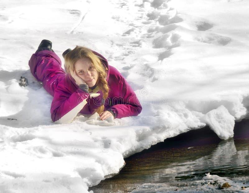 Fille heureuse se trouvant sur la neige en hiver photos stock