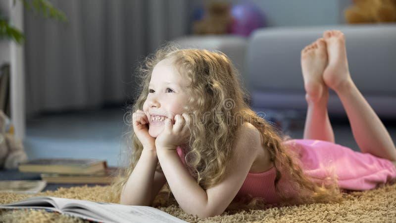 Fille heureuse se trouvant sur le plancher, le livre de lecture, l'imagination se d?veloppante et la cr?ativit? photos libres de droits