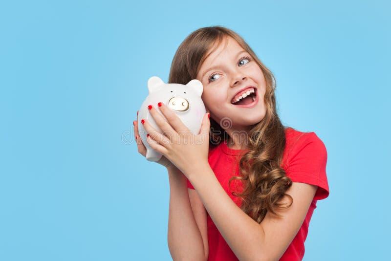 Fille heureuse secouant la boîte porcine photographie stock libre de droits