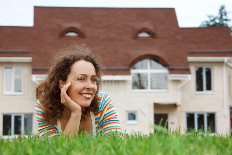 Fille heureuse sur la pelouse devant la maison neuve photos libres de droits