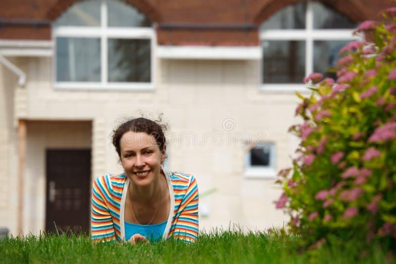 Fille heureuse sur la pelouse devant la maison neuve photos stock
