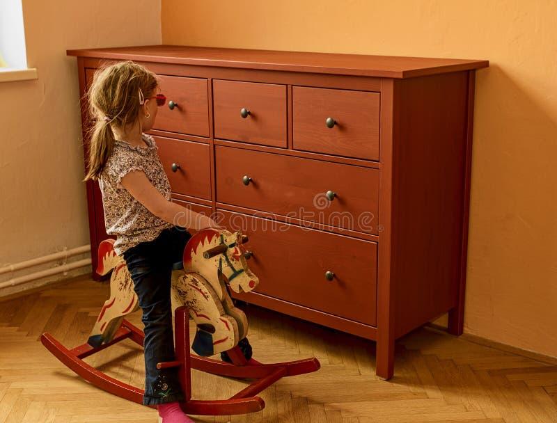 Fille heureuse sur le cheval d'oscillation La petite fille porte les lunettes rouges photographie stock
