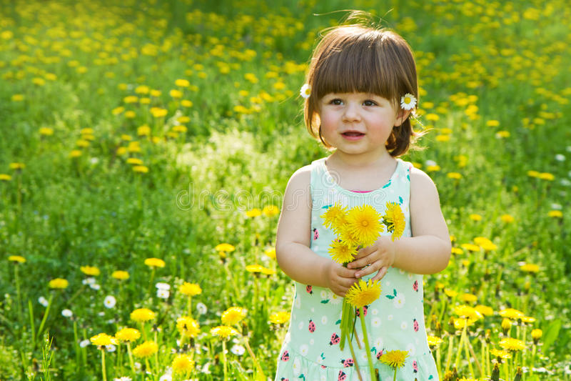 Fille heureuse sur le pré avec les fleurs blanches image stock