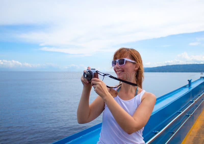Fille heureuse sur le revêtement de croisière faisant la photo Jeune femme avec le photocamera images stock