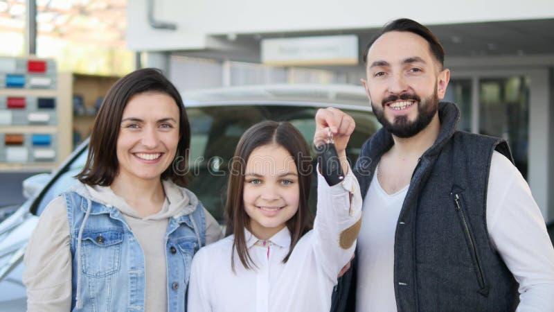 Fille heureuse tenant des clés dans la nouvelle voiture familiale image stock