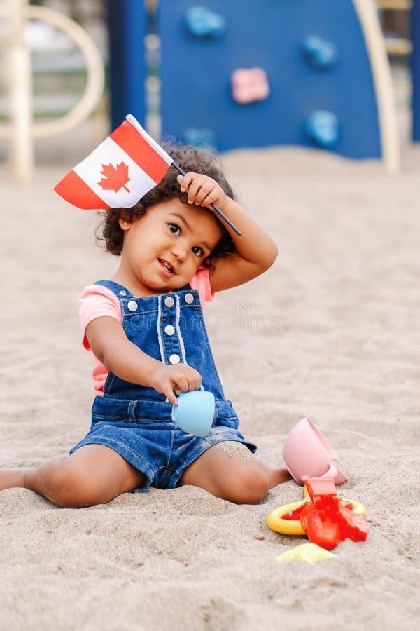 fille hispanique latine d'enfant en bas âge de bébé tenant le drapeau canadien de ondulation photographie stock libre de droits