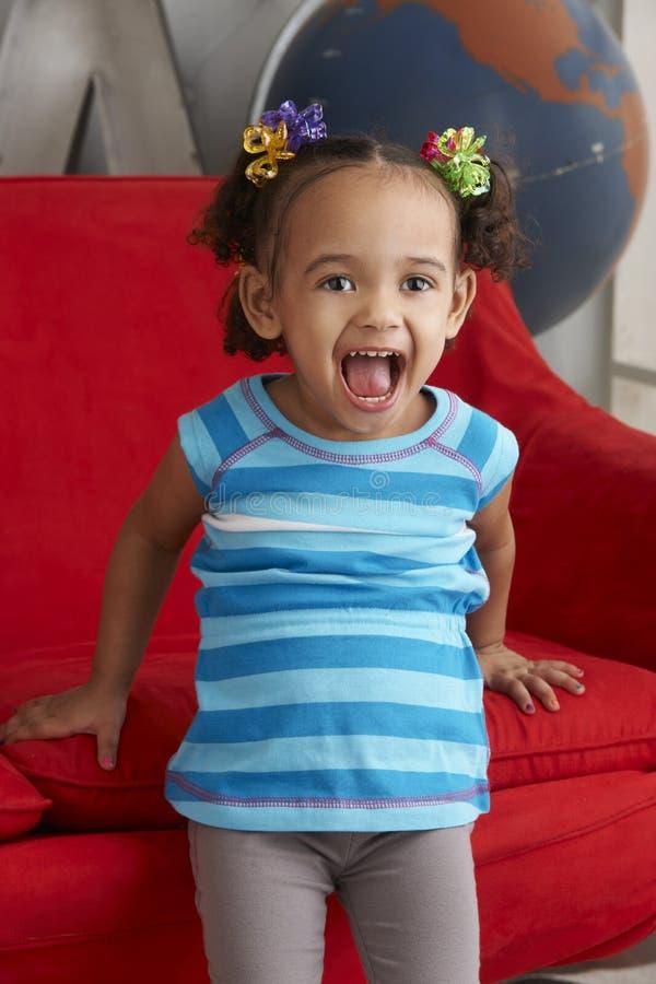 Enfant en bas âge riant à la maison photo stock