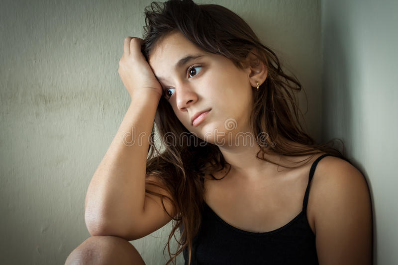 Fille hispanique triste s'asseyant dans un coin photo libre de droits