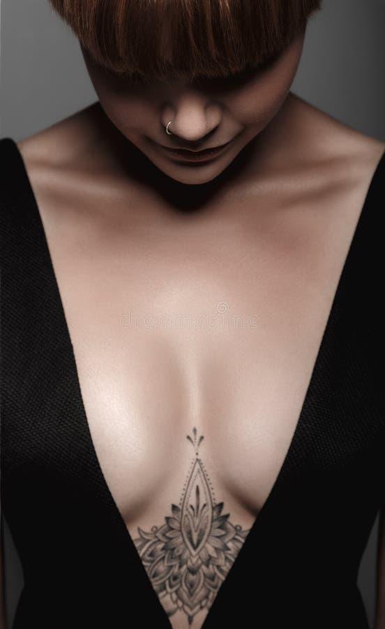 Fille humide sexy chaude avec le tatouage dans le noir image stock