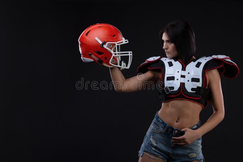 Fille incroyablement belle et sportive de brune dans shoulderpads et un casque de football américain démontrant l'ABS étonnant re photo stock