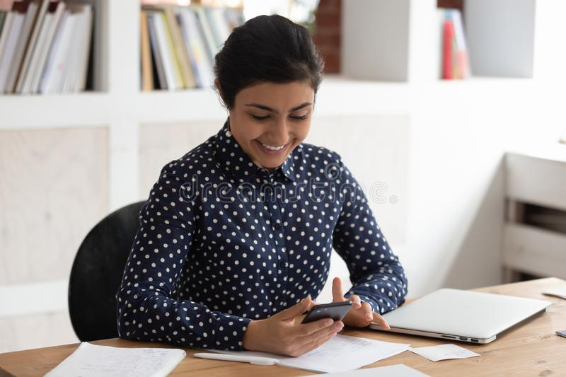 Fille indienne de sourire distraite de l'étude utilisant le téléphone portable photo stock