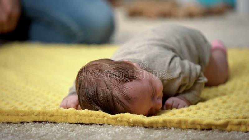 Fille infantile adorable minuscule se trouvant sur le ventre essayant de ramper, d?veloppement nouveau-n? image stock