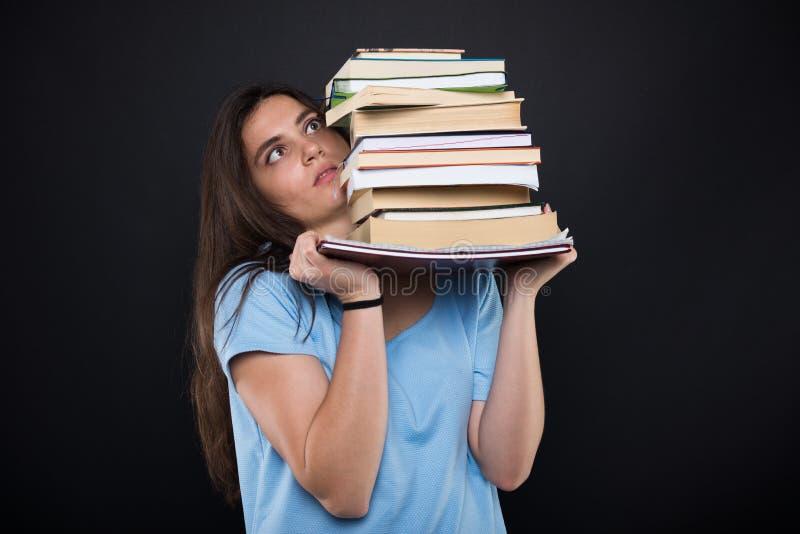 Fille inquiétée d'étudiant tenant une pile des livres photographie stock libre de droits