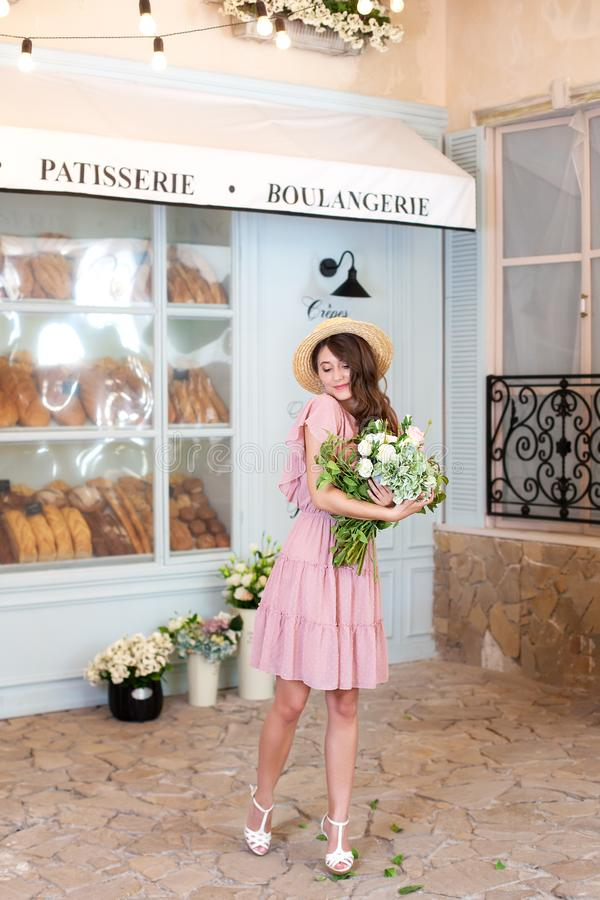 Fille insouciante appréciant un groupe de fleurs Portrait d'une belle jeune femme près du café Fille heureuse avec un bouquet des photographie stock libre de droits