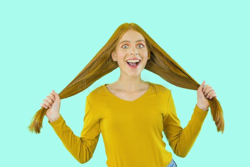 Fille insouciante joyeuse avec de beaux longs cheveux rouges tenant des cheveux dans les deux sourires de mains avec enthousiasme image stock