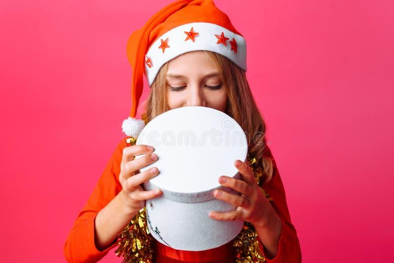 Fille intéressée dans le chapeau de Santa et avec la tresse autour de sa pièce en t de cou image libre de droits