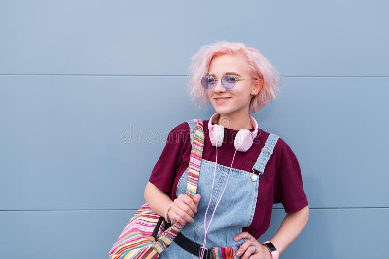 Fille intelligente heureuse avec les cheveux roses se tenant dans la perspective d'un mur bleu examinant la caméra et le sourire photo stock