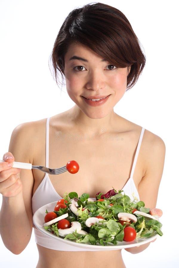 Fille japonaise de sourire mangeant le repas sain de salade image libre de droits