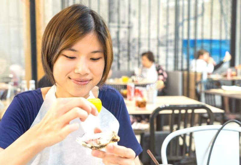 Fille japonaise mangeant l'huître fraîche photo libre de droits