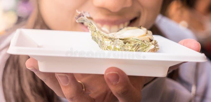 Fille japonaise mangeant l'huître fraîche d'Hiroshima images stock
