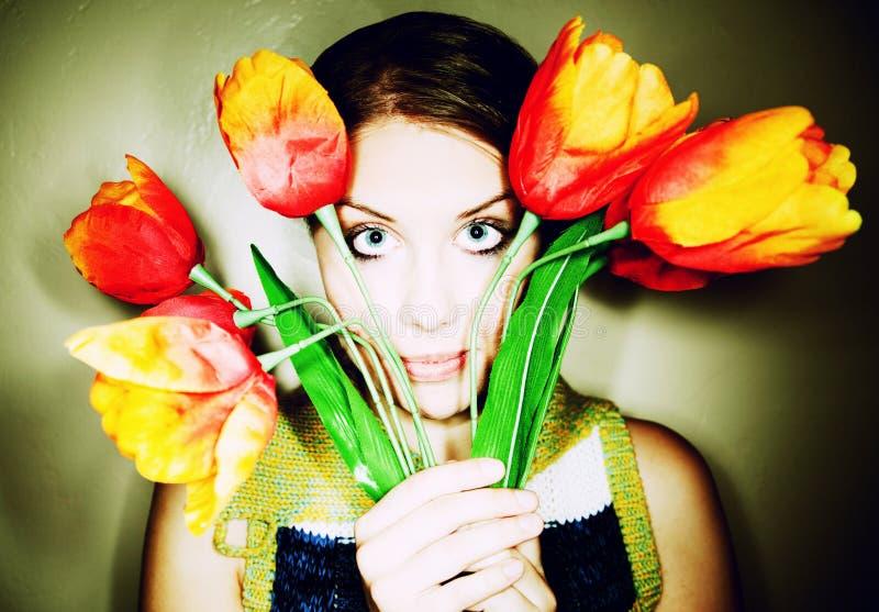 Fille jetant un coup d'oeil à l'extérieur par derrière les fleurs en plastique photos libres de droits