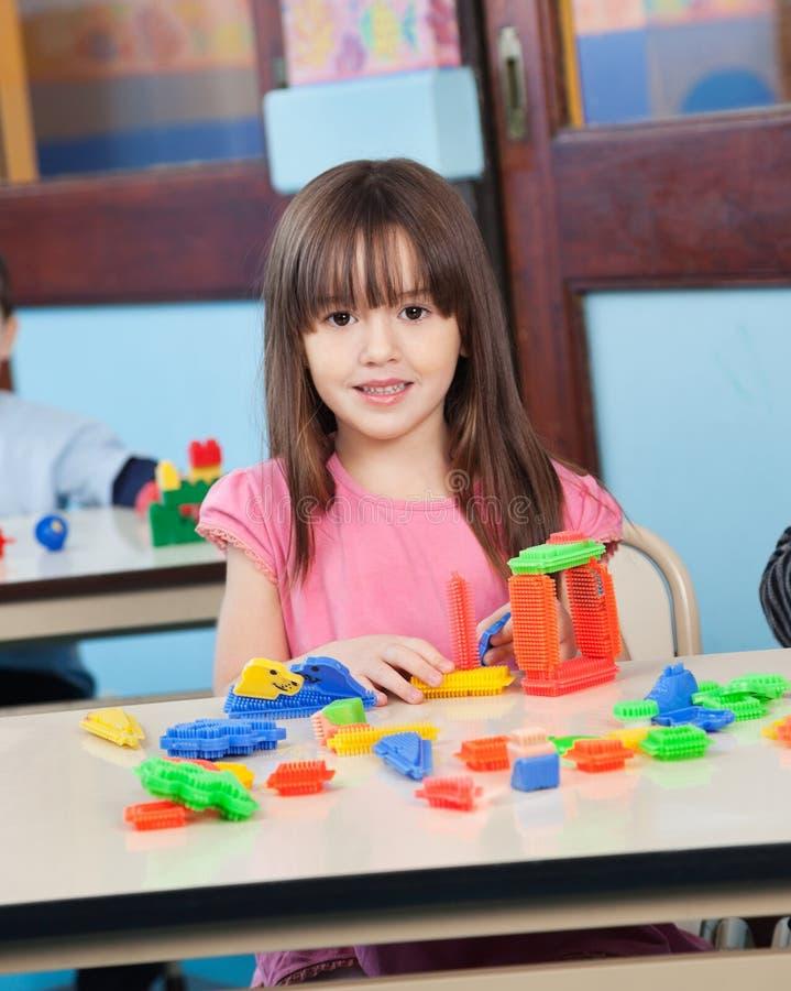 Fille jouant avec des blocs de construction dans l'école maternelle image libre de droits