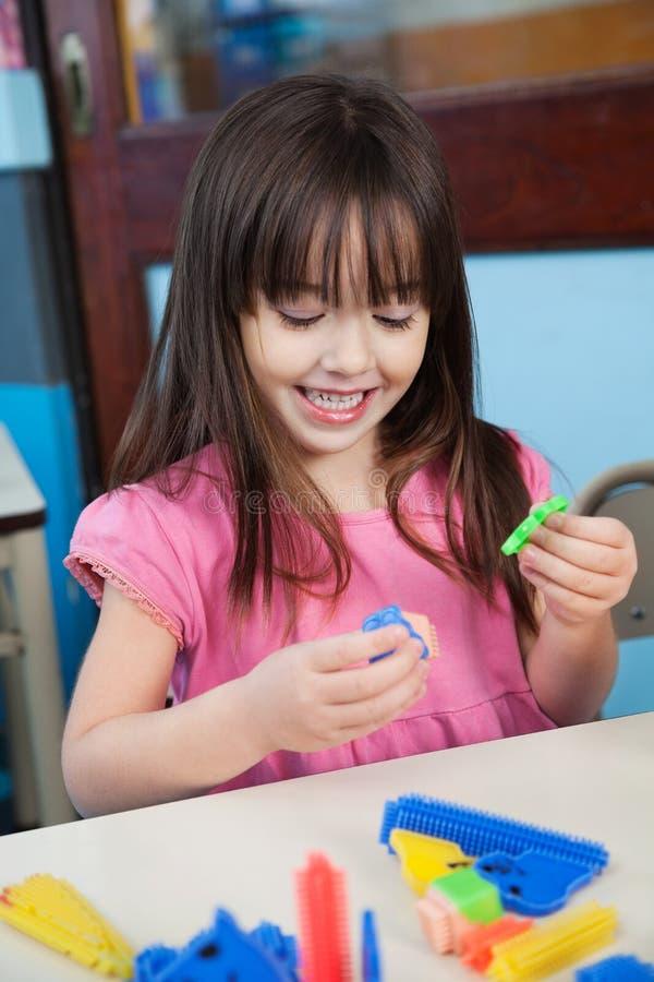 Fille jouant avec des blocs de construction dans la salle de classe photographie stock libre de droits