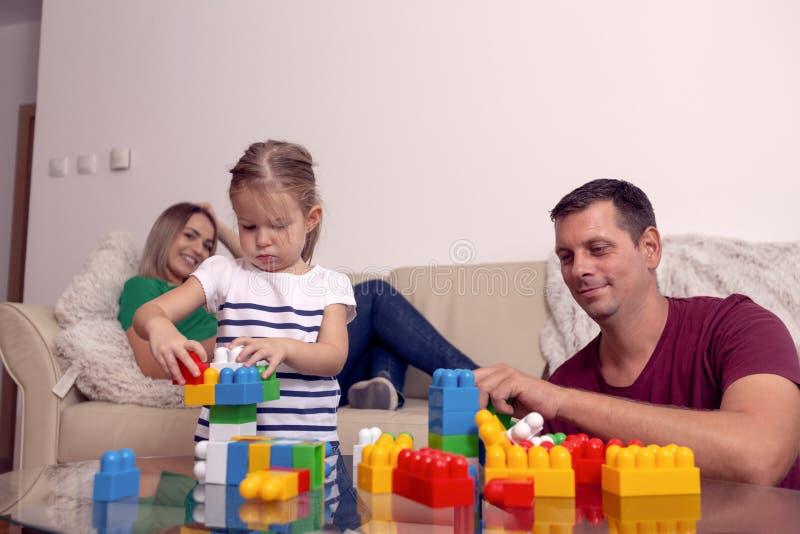 Fille jouant avec des cubes en m?re et en p?re ensemble ? la maison images stock