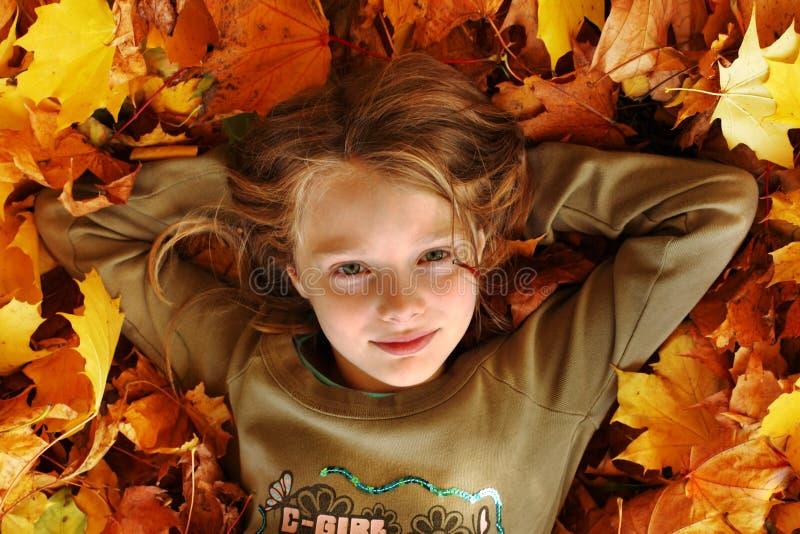 Fille jouant avec des lames d'automne vers le haut dans le ciel photos libres de droits