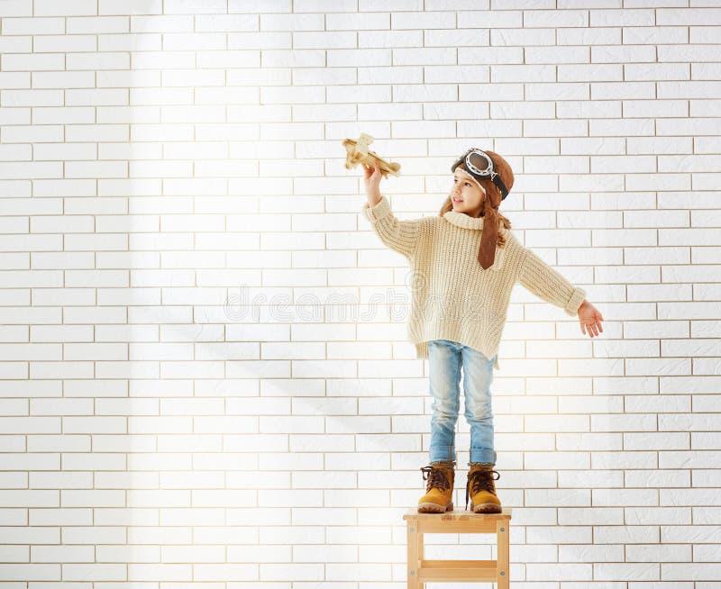 Fille jouant avec l'avion de jouet image stock