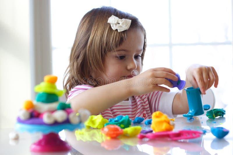 Fille jouant avec la pâte de pièce photo stock