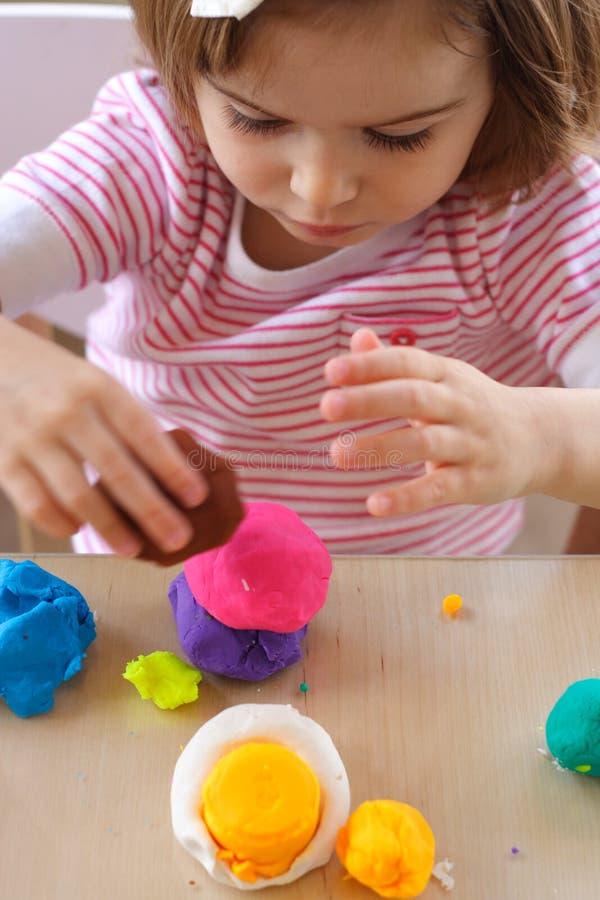 Fille jouant avec la pâte de pièce photo libre de droits