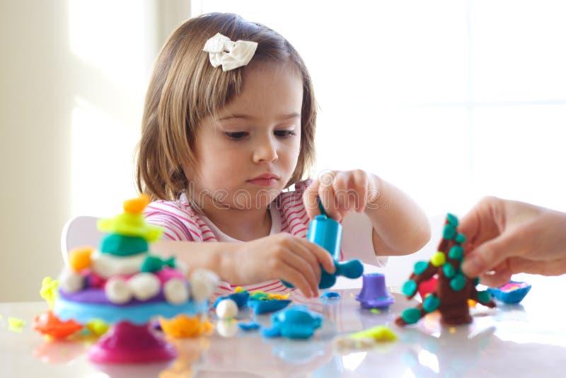 Fille jouant avec la pâte de pièce photographie stock libre de droits