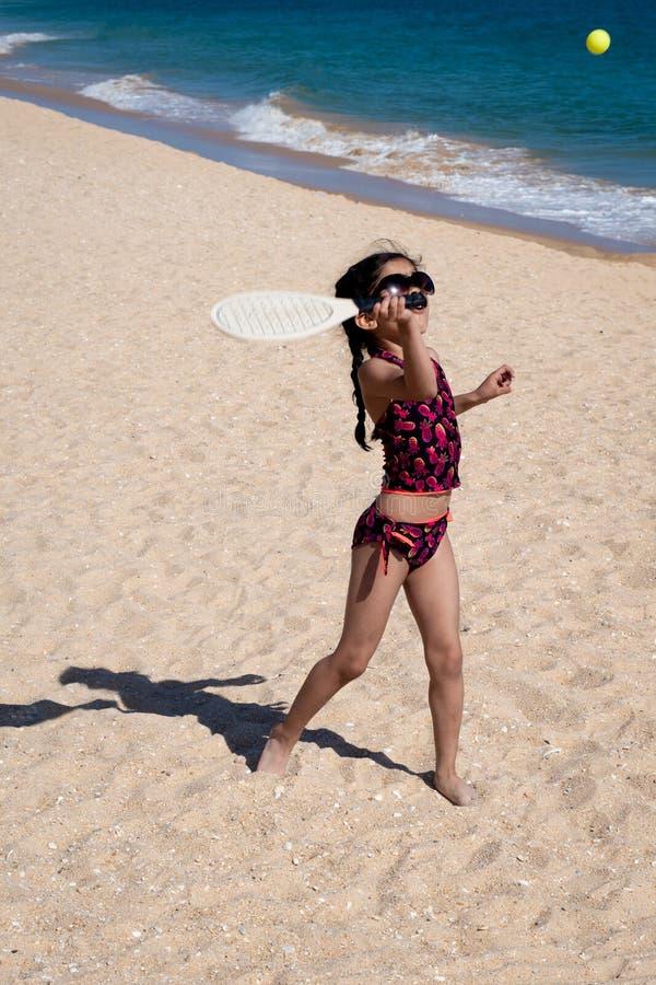 Fille jouant avec la raquette à une plage des vacances images libres de droits