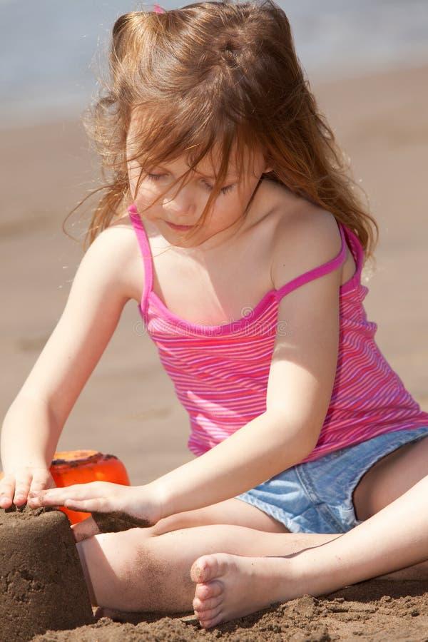 Fille jouant avec le sable photos stock