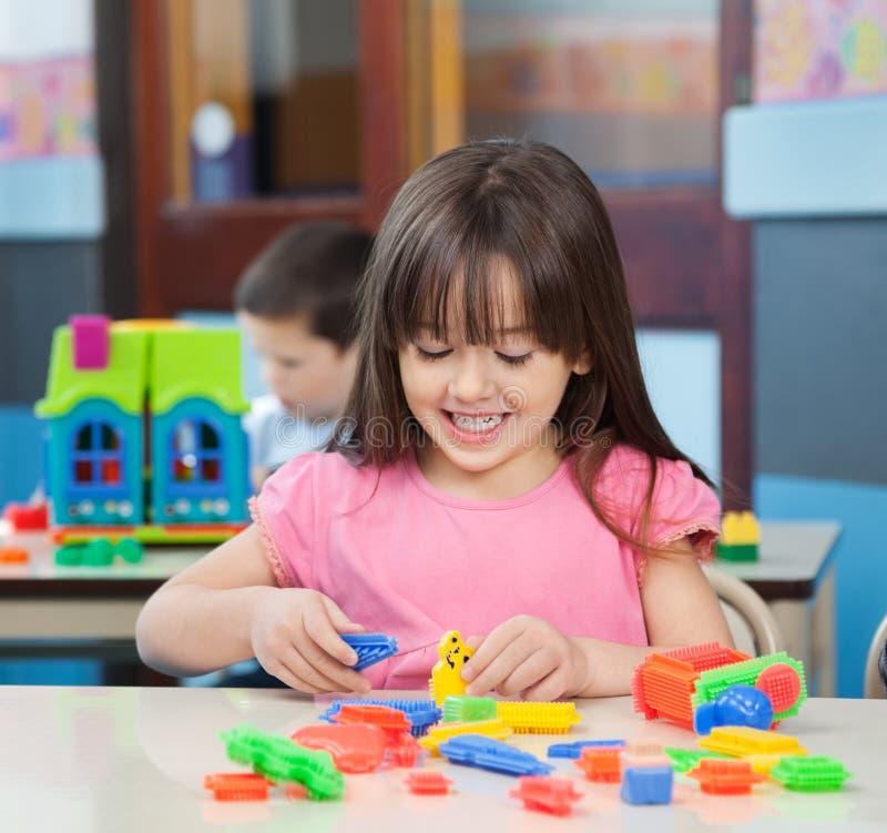 Fille jouant avec les blocs colorés dans la salle de classe image libre de droits