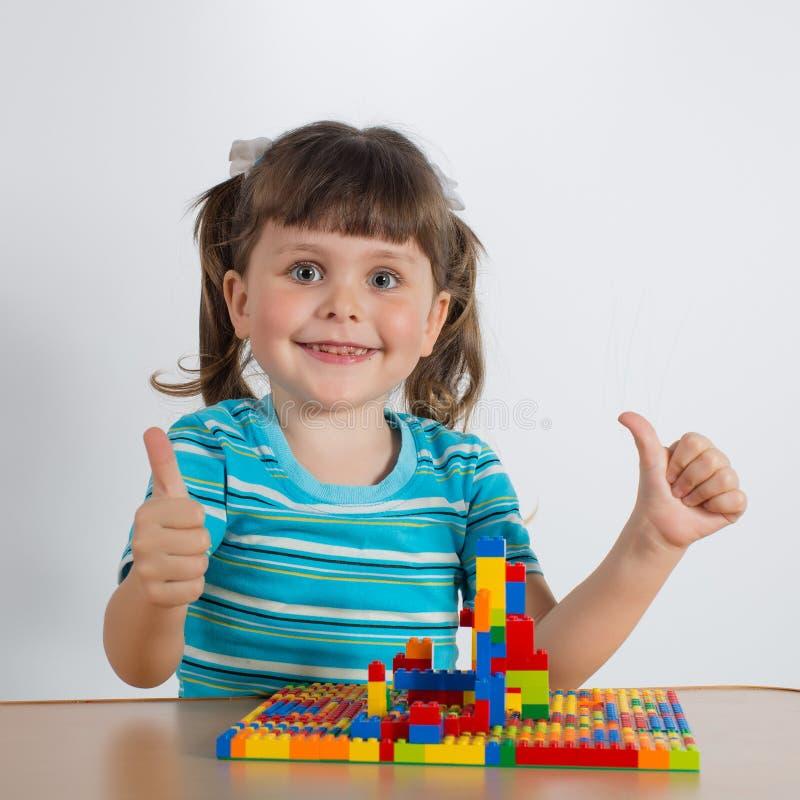 Fille jouant avec les cubes se reliants en jouet images libres de droits