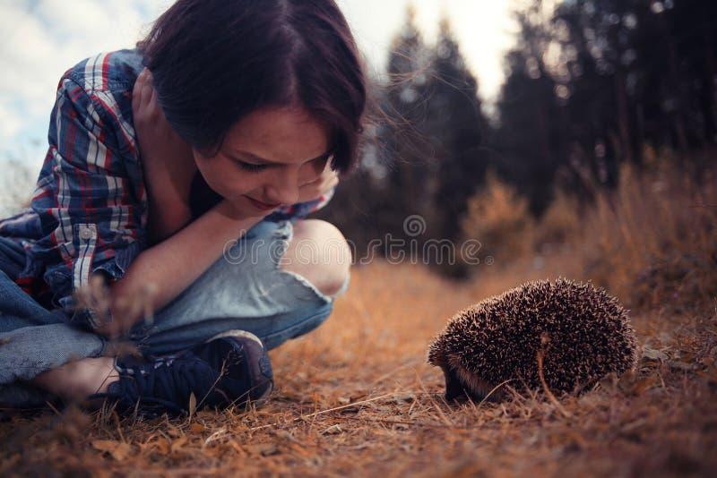 Fille jouant avec un hérisson images stock