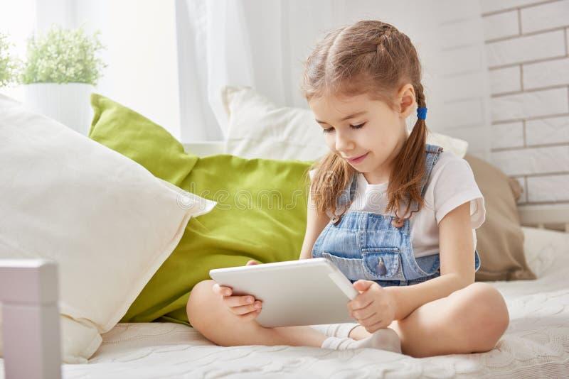 Fille jouant dans la tablette images libres de droits