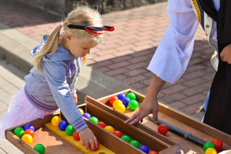 Fille jouant dehors avec un pirate à une recherche de table, formation de mémoire avec les boules colorées photo libre de droits