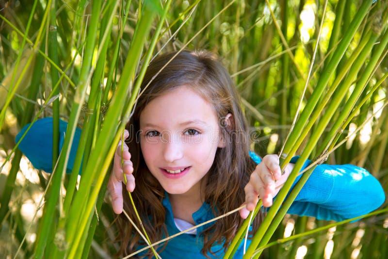 Fille jouant en nature piaulant des cannes vertes photographie stock